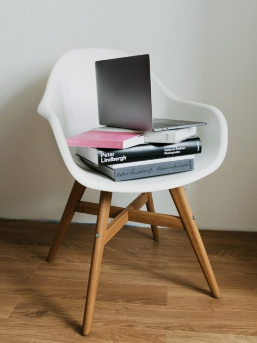 white-chair-with-stack-of-books-and-laptop-on-top-3847677